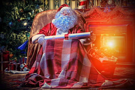 Santa Claus with a list of Christmas presents sitting in a comfortable chair near the fireplace at home.  Stock Photo - 16216167