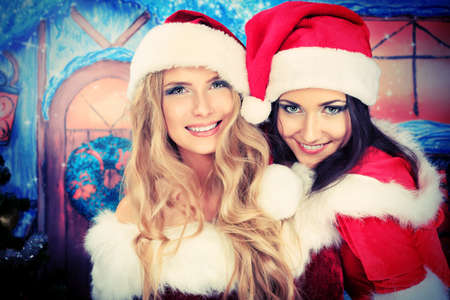 Two beautiful young women in Christmas clothes posing over Christmas background. photo