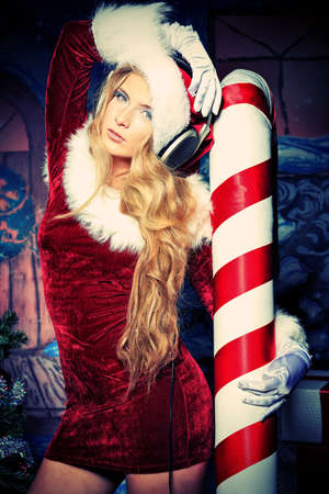 sexy headphones: Beautiful young woman in Santa Claus clothes and headphones over Christmas background. Stock Photo