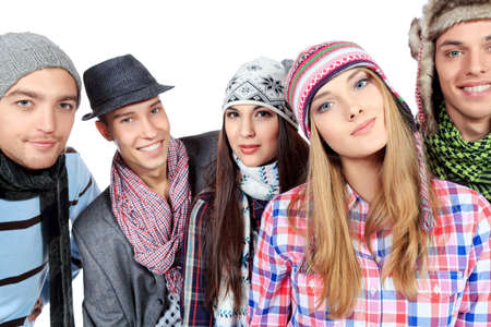 spring hat: Group of cheerful young people in warm clothes standing together. Friendship. Isolated over white. Stock Photo