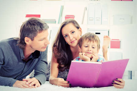 Portrait of a happy parents reading a book with their son. Stock Photo - 16226116