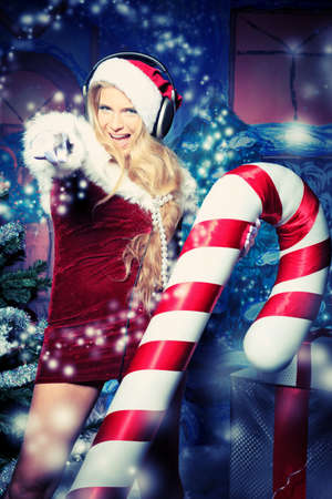 dj party: Beautiful young woman in Santa Claus clothes and headphones over Christmas background. Stock Photo