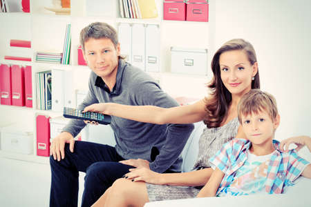 Happy family emotionally watching television at home. photo
