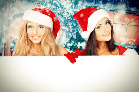 snow maiden: Two sexy young women in Christmas clothes holding white board over Christmas background.