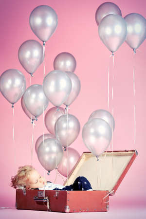 Little boy is sleeping in the old suitcase under many balloons. Stock Photo - 16273163