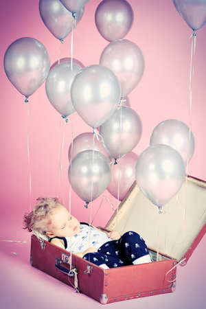 Little boy is sleeping in the old suitcase under many balloons.  Stock Photo - 16273159