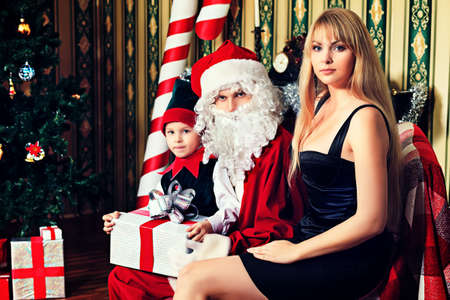 Portrait of a happy family spending Christmas time with Santa Claus at home. Stock Photo - 16273183