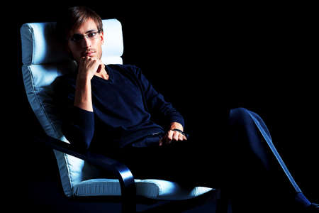 Portrait of a handsome man sitting in the armchair over black background. Stock Photo - 16383196