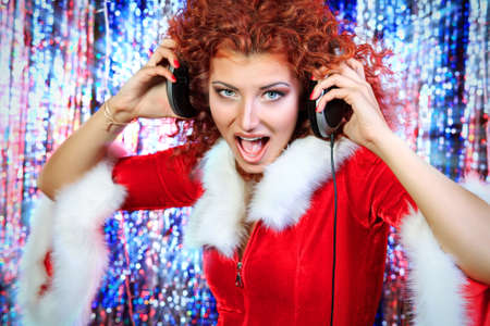 Attractive DJ girl mixing up some Christmas cheer. Disco lights in the background.  photo