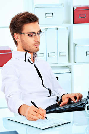 Handsome businessman is working on a laptop at the office. photo