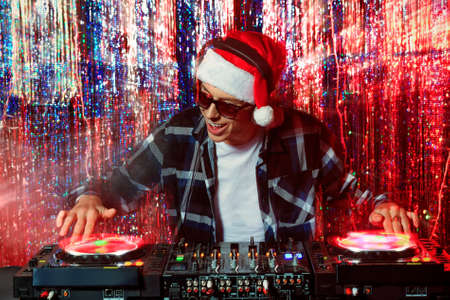DJ mixing up some Christmas cheer. Disco lights in the background.  photo
