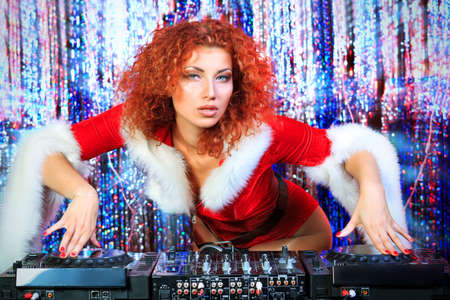snow maiden: Attractive DJ girl mixing up some Christmas cheer. Disco lights in the background.