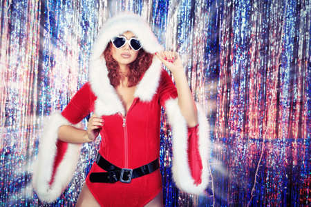 Attractive young woman in Christmas clothes on a party. Disco lights in the background. photo