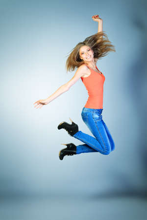 woman jumping: Full length portrait of a happy young woman jumping at studio. Stock Photo