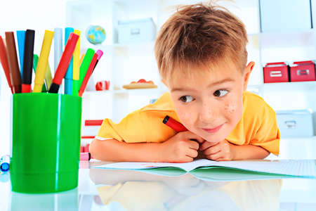 primary education: Little boy drawing in his notebook at home. Stock Photo