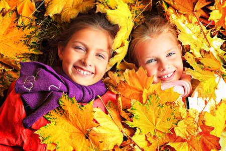 family and health: Portrait of two cute girls sisters lying on the leaves at the autumn park. Stock Photo