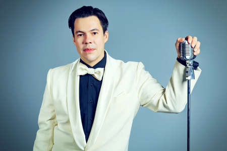 Portrait of a man professional singer in retro style posing in costume at studio. photo