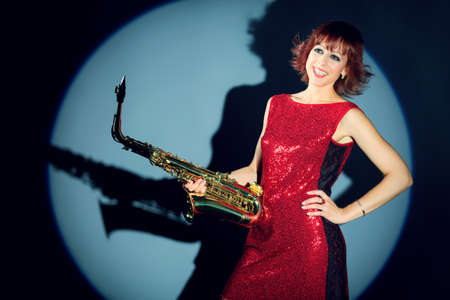 jazz singer: Professional musician posing with her saxophone at studio.