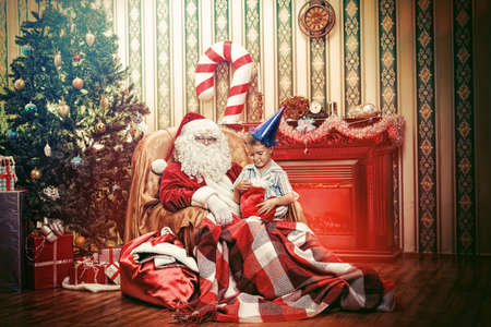 Santa Claus giving a present to a little cute boy at home. Stock Photo - 16354471