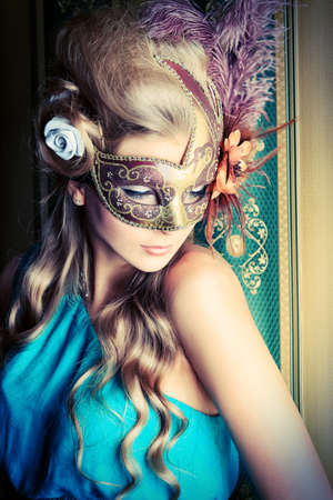 costume ball: Beautiful young woman in a carnival mask over vintage background. Stock Photo
