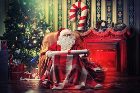 fireplace christmas: Santa Claus with a list of Christmas presents sitting in a comfortable chair near the fireplace at home.
