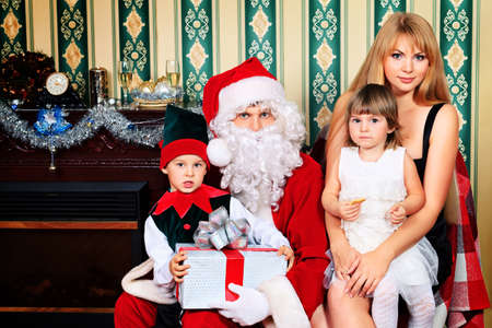 Portrait of a happy family spending Christmas time with Santa Claus at home. photo
