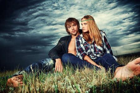 mujer hippie: Joven pareja rom�ntica en ropa casual sentado juntos en un campo en un fondo del cielo tormenta.
