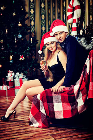 Happy young couple celebrating Christmas near the Christmas tree and fireplace at home. photo
