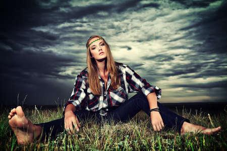 mujer hippie: Mujer rom�ntica joven en ropa casual sentado en un campo en un fondo del cielo tormenta.