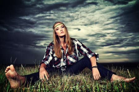 Romantic young woman in casual clothes sitting in a field on a background of the storm sky.  photo