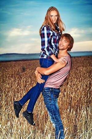 country boy: Romantic young couple in casual clothes standing together in a wheat field on a background of the storm sky.