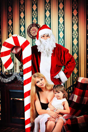 Portrait of a happy family spending Christmas time with Santa Claus at home. Stock Photo - 16447538