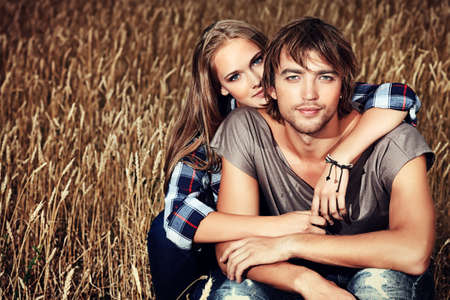 country style: Romantic young couple in casual clothes sitting together in a wheat field.