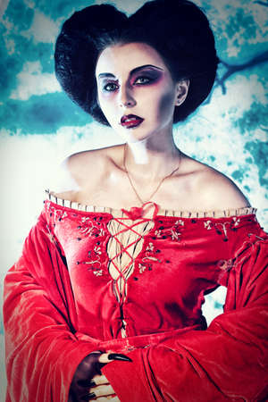 Portrait of a beautiful female vampire over moonlight background. photo