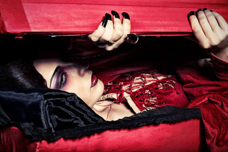 bloodthirsty: Bloodthirsty female vampire rises from the coffin on the night cemetery.