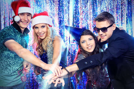 Group of cheerful young people celebrating Christmas at the nightclub. Stock Photo - 16447661