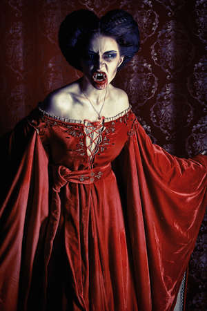 Portrait of a bloodthirsty female vampire over red vintage background.