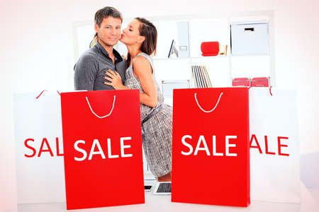 Seasonal sale: happy couple holding shopping bags inside of a store. photo