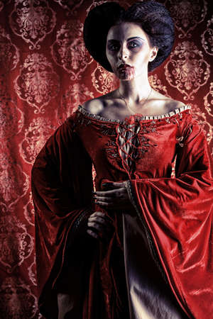 beautiful vampire: Portrait of a beautiful female vampire over red vintage background. Stock Photo