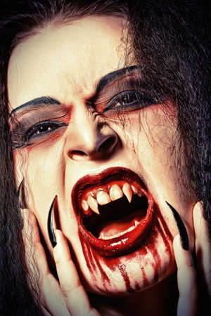 fangs: Close-up portrait of a bloodthirsty female vampire. Stock Photo