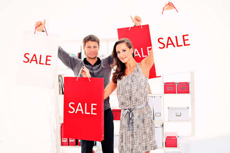 sale shop: Seasonal sale: happy couple holding shopping bags inside of a store.