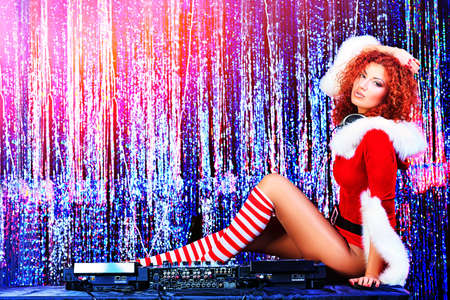 Attractive DJ girl mixing up some Christmas cheer. Disco lights in the background.  Stock Photo - 16548663