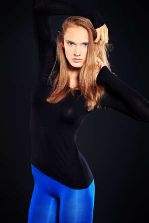 Attractive young woman in fitting clothing posing at studio.