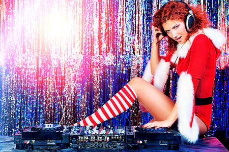 Attractive DJ girl mixing up some Christmas cheer. Disco lights in the background.  Stock Photo - 16548659