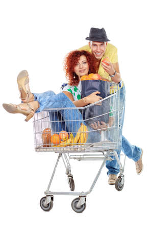 Cheerful couple with a shopping trolley  Isolated over white background  photo