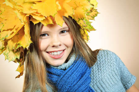 Portrait of a smiling girl in autumn clothes and a hat of maple leaves Stock Photo - 16522746