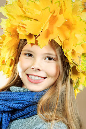 Portrait of a smiling girl in autumn clothes and a hat of maple leaves  Stock Photo - 16522748