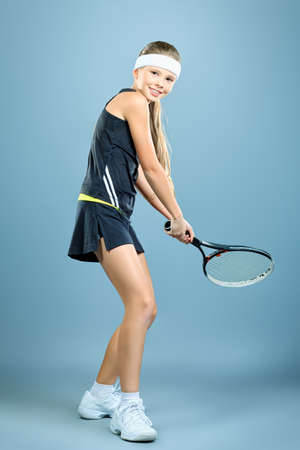 Portrait of a girl tennis player holding tennis racket and tennis ball  Studio shot   Stock Photo