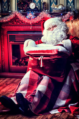 Santa Claus with gifts sitting in a comfortable chair near the fireplace at home.  photo