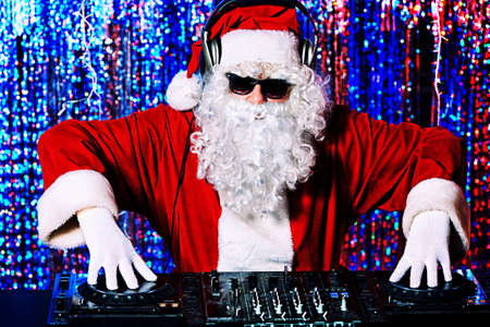 dj party: DJ Santa Claus mixing up some Christmas cheer. Disco lights in the background.